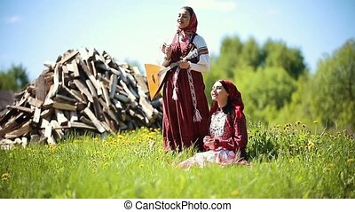 Two young women in traditional russian clothes singing songs...