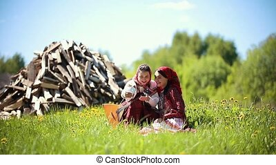 Two young women in traditional russian clothes sitting on...