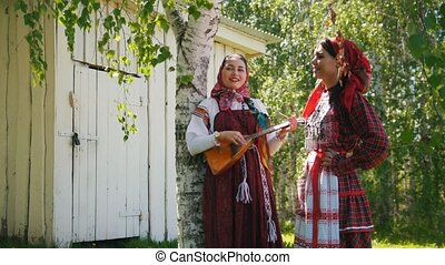 Two young women in traditional Russian clothes standing near...