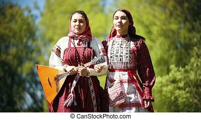 Two young women in traditional russian clothes walking in...
