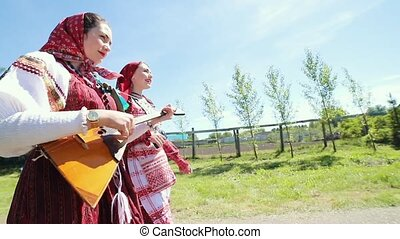 Two young women in traditional russian clothes walking on...