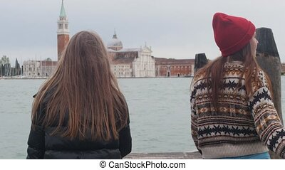 Two young women is walking along the pier. One of them eating icecream - then she offers ice cream to her friend. Mid shot