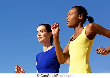 Two young women jogging against blue sky