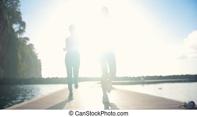 Two young women jogging on the bridge above the sea