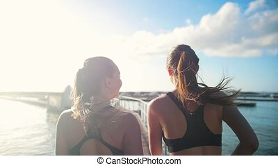 Two young women jogging on the bridge towards the sea port in sunny day