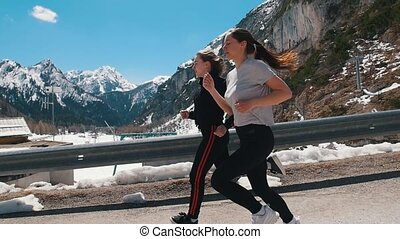 Two young women jogging on the road - Dolomites, Italy