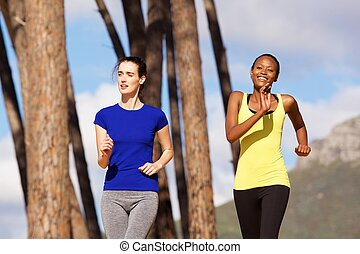 Two young women jogging together outdoors