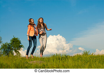 Two young women jumping against blue sky