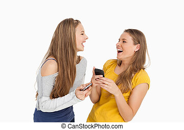 Two young women laughing while holding their cellphones...