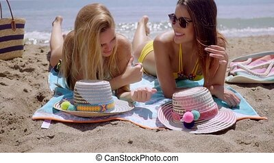 Two young women lying sun tanning on a beach