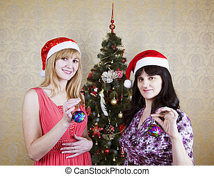 two young women near a christmas tree