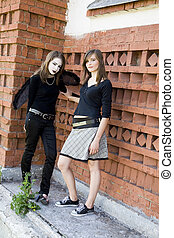 Two Young Women Near A Wall