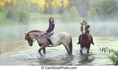 Two young women on horseback standing in the lake, horses...