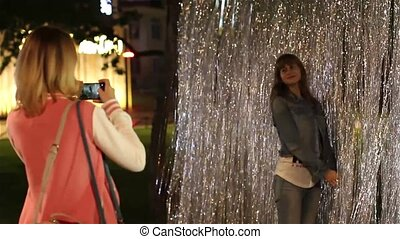 Two young women photographed in shiny tinsel