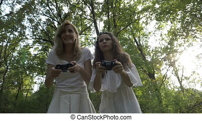 Two young women playing video games outdoor with gamer...