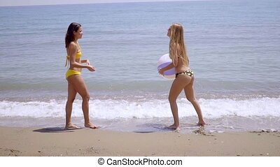 Two young women playing with a beach ball