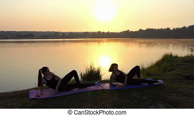 Two Young Women Practice Yoga Lying on Mats on a Lake Bank at Sunset
