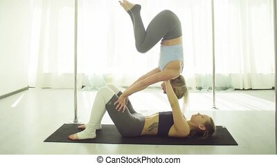 Two young women practicing acrobatic yoga. - Two young women...