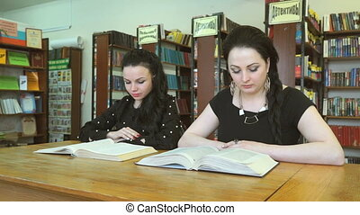 Two young women reading textbooks at library