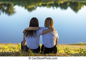 Two young women rear view hugging while sitting on the grass near the river in autumn. Friends leaned on each other in the park