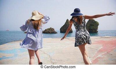 Two young women run along the promenade directly to the...