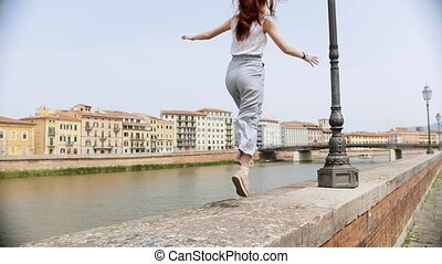 Two young women run and jumping along the curb by the river....