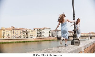 Two young women running for the each other on the edge of...