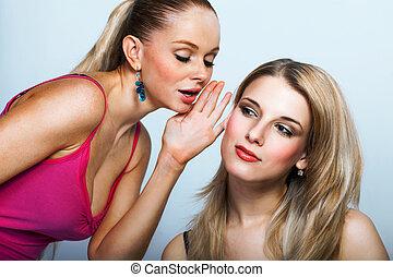 Two young women sharing secret