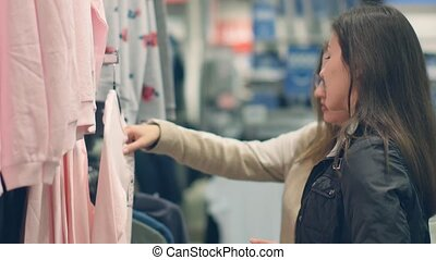Two young women shop at the store choosing warm clothes