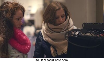 Two young women shop at the store choosing warm winter clothes