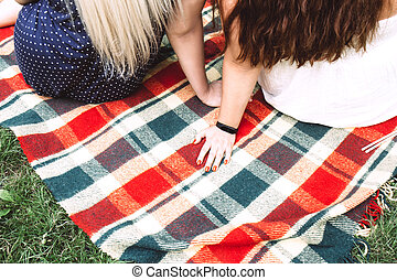 Two young women sit side by side on a bright plaid blanket in nature