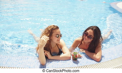Two young women sitting by the poolside clear water in resort hotel on vacation