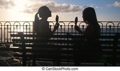 Two young women sitting on the quay of the sea and eating...