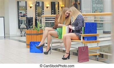 Two young women sitting with shopping bags and smiling. Slow motion