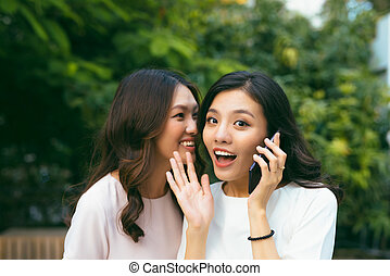 Two young women socializing outdoors.