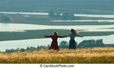Two young women spinning arms outstretched on the field in...
