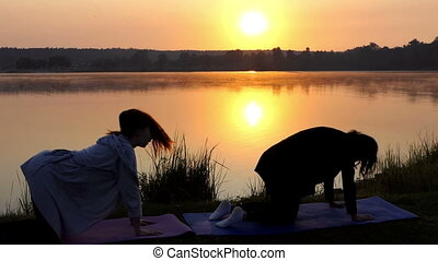 Two Young Women Stand on All Fours And Train Breathing on a Lake Bank at Sunset