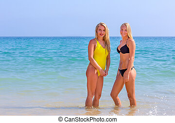 Two young women standing in blue sea water