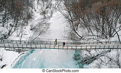 Two young women standing on the snowy bridge in the winter forest