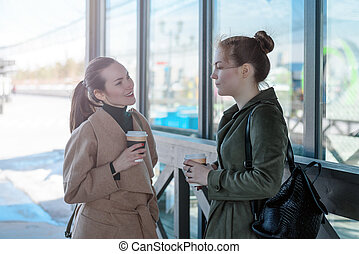 Two young women talking on the streets with cups of coffee in their hands
