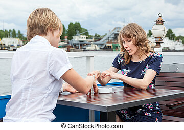 Two young women talking together while sitting at the table in summer cafe