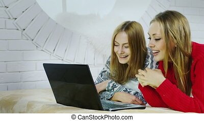 Two young women talking with a laptop