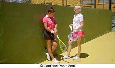 Two young women tennis players standing chatting
