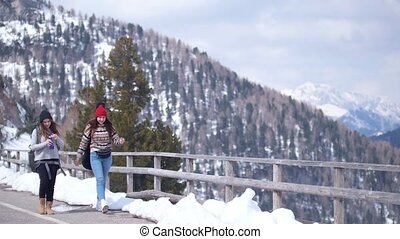 Two young women tourist traveling in Dolomites with big...