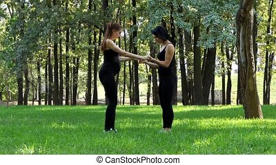 Two young women train in black suits in a park