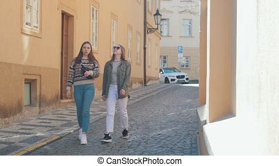 Two young women travelers walking on the narrow streets and...