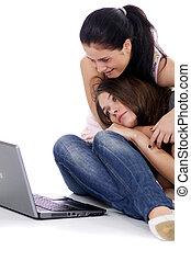Two young women using laptop