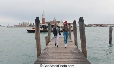 Two young women walk along the pier directly to the camera....