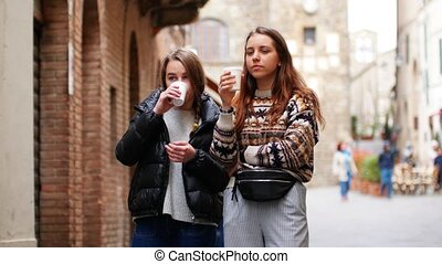 Two young women walk the streets. People pass by. Middle ...