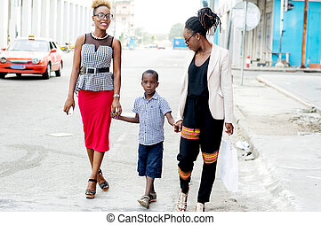 Two young women walk with little boy.